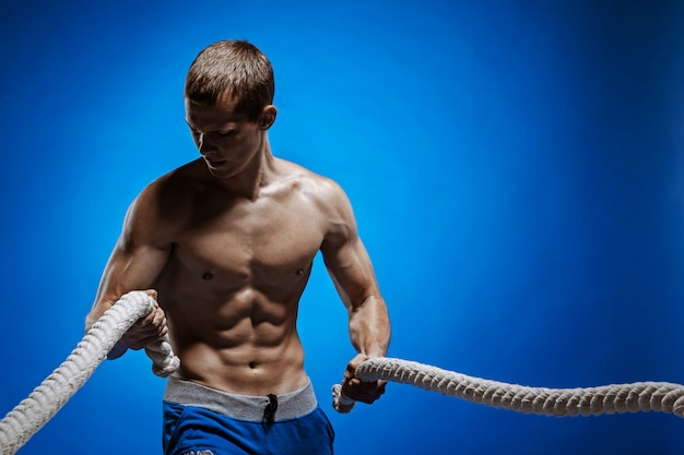 Giovane adatto con il bello torso e una corda sul blu