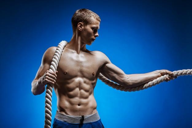 Giovane adatto con il bello torso e una corda sulla parete blu