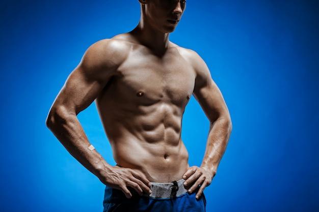 Giovane adatto con il bello torso sulla parete blu