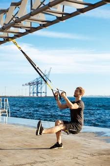 Giovane addestramento sportivo dell'uomo con trx vicino al mare di mattina.