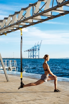 Giovane addestramento sportivo della donna con trx vicino al mare di mattina.