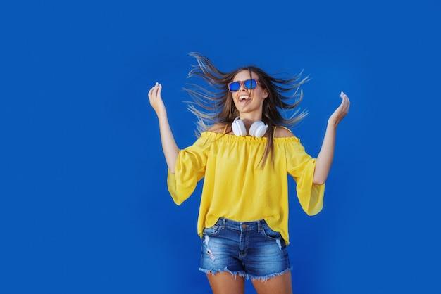 Giovane adolescente caucasico allegro negli shorts gialli del denim e della blusa che salta davanti alla parete blu.