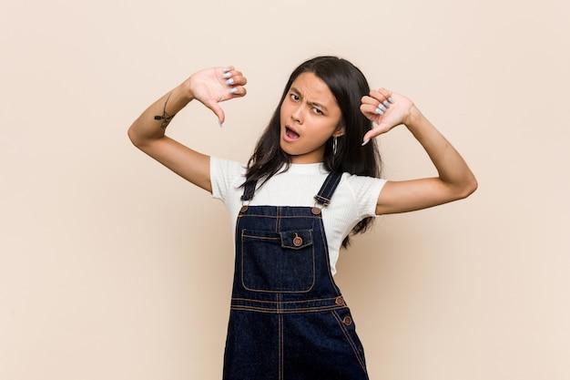 Giovane adolescente cinese carino giovane donna bionda che indossa un cappotto contro un muro rosa che mostra il pollice verso il basso ed esprimere antipatia.