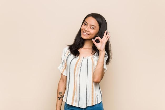 Giovane adolescente cinese carino giovane donna bionda che indossa un cappotto contro un muro rosa strizza l'occhio e tiene un gesto giusto con la mano.