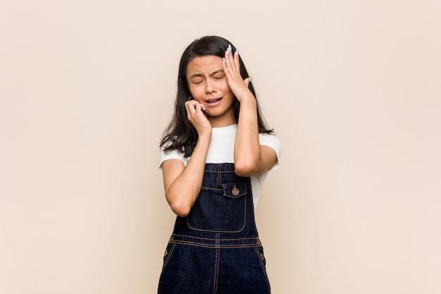 Giovane adolescente cinese carino giovane donna bionda che indossa un cappotto piagnucolando e piangendo sconsolato.