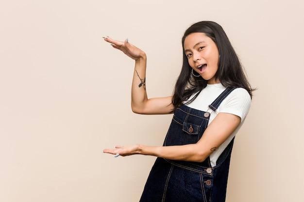 Giovane adolescente cinese carino giovane donna bionda che indossa un cappotto rosa scioccato e stupito in possesso di una copia spazio tra le mani.
