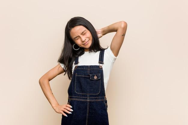 Giovane adolescente cinese carino giovane donna bionda che indossa un cappotto sul dolore al collo sofferenza rosa a causa di uno stile di vita sedentario.