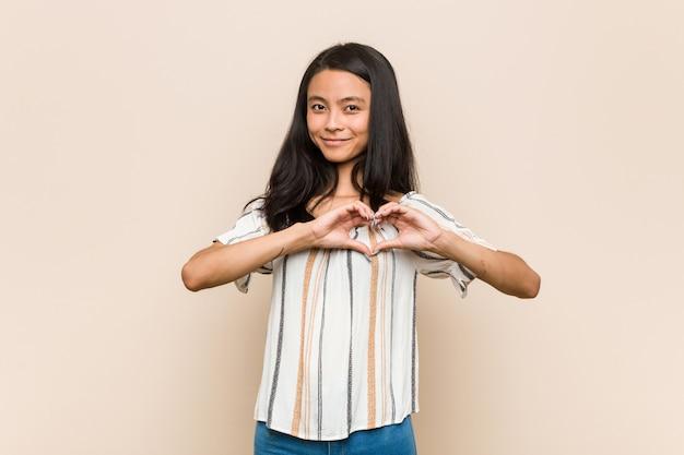 Giovane adolescente cinese sveglio che sorride e che mostra una forma del cuore con le mani