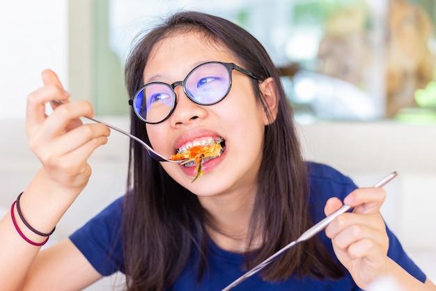Giovane adolescente femminile con apparecchi ortodontici mangiare e mordere la sua pizza