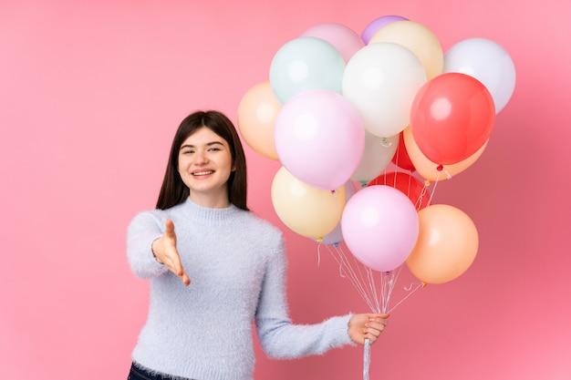 Giovane adolescente in possesso di un sacco di palloncini handshake dopo buon affare