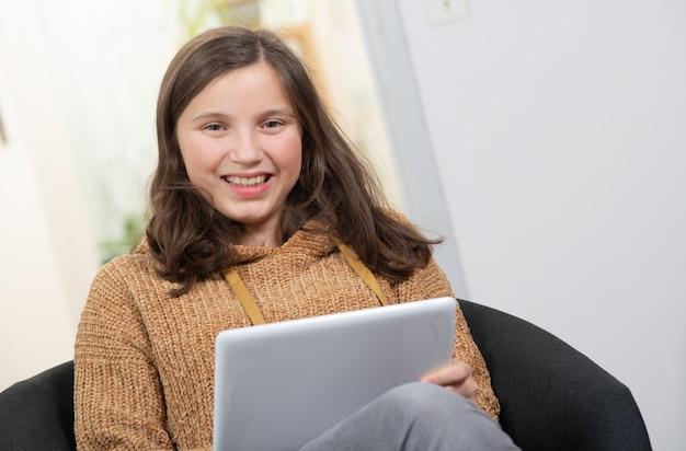Giovane adolescente sorridente utilizzando un tablet pc