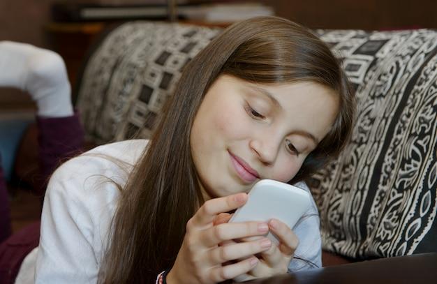 Giovane adolescente sul divano invia un messaggio di testo