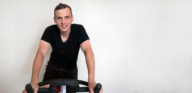 Giovane adulto attraente uomo impegnato su una bici da casa sorridendo e guardando la telecamera su uno sfondo bianco, copia dello spazio