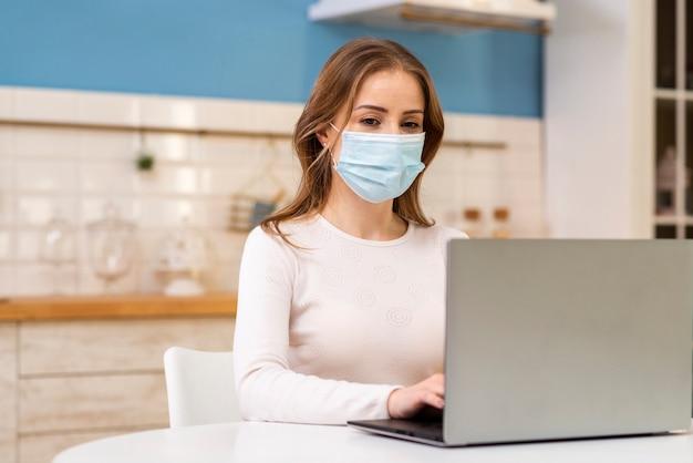 Giovane adulto che indossa una maschera di protezione in cucina
