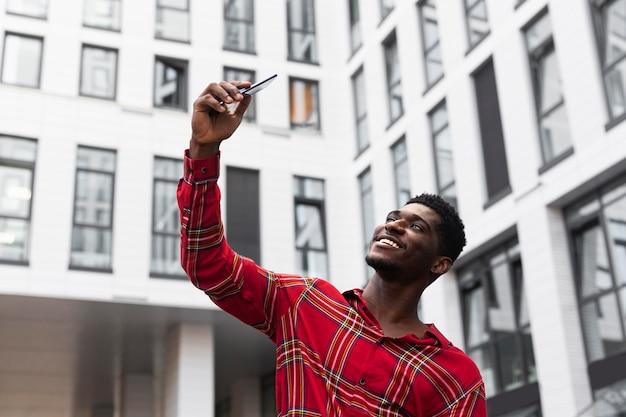 Giovane adulto in camicia rossa che cattura una foto di auto