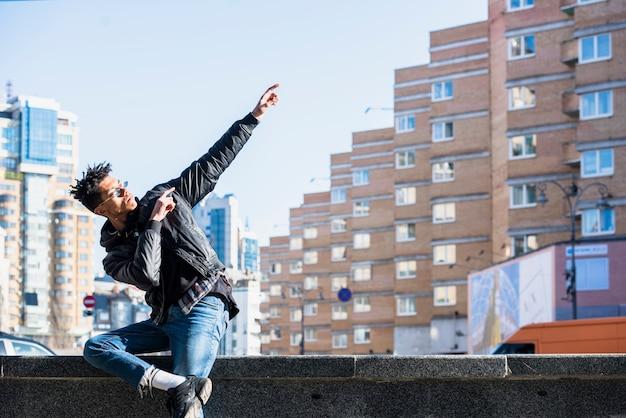 Giovane africano che si siede sulla parete che gesturing davanti alle costruzioni nella città