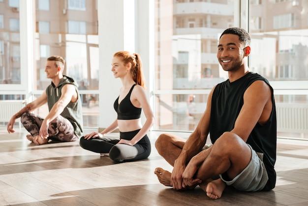 Giovane africano felice che si siede e che fa yoga nel gruppo