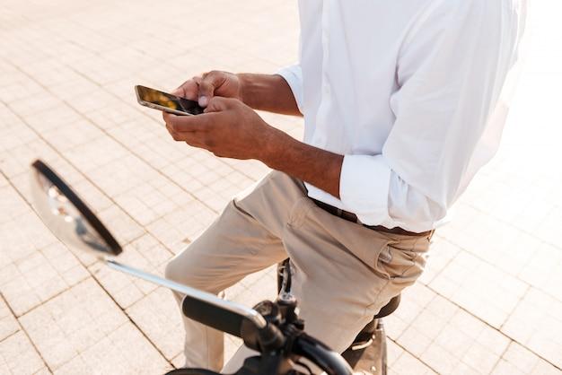 Giovane africano seduto su una moderna moto all'aperto e utilizzando smartphone