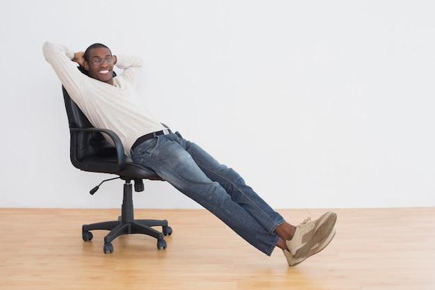 Giovane afro casuale che si siede sulla sedia dell'ufficio in una stanza vuota