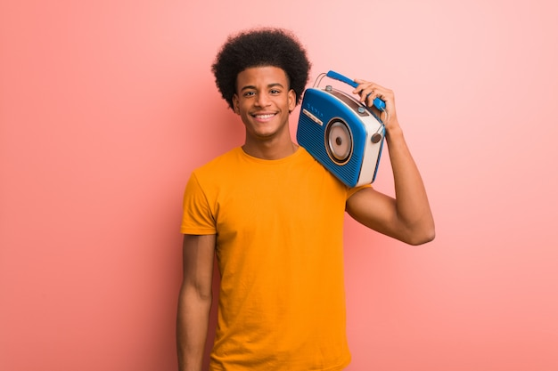 Giovane afroamericano che giudica allegra una radio d'annata con un grande sorriso