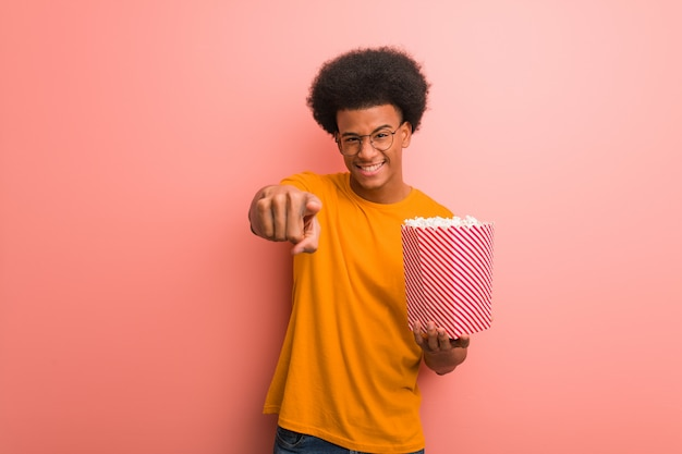 Giovane afroamericano che giudica un secchio del popcorn allegro e che sorride indicando la parte anteriore