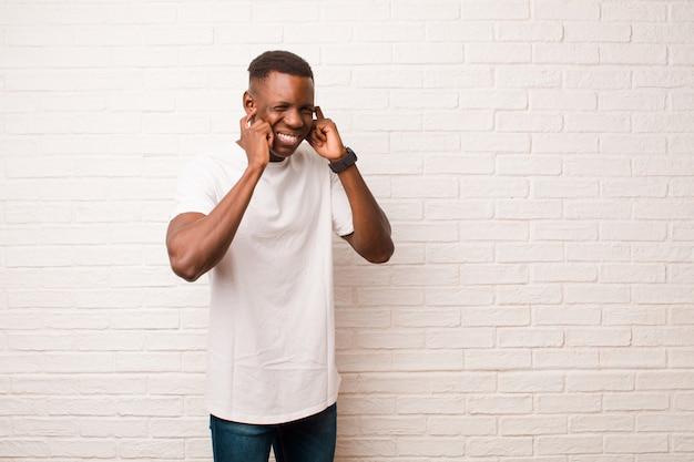Giovane afroamericano che sembra arrabbiato, stressato e infastidito, coprendo entrambe le orecchie con un rumore assordante, suono o musica ad alto volume sul muro di mattoni