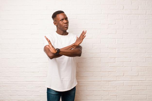 Giovane afroamericano che sembra infastidito e stanco del tuo atteggiamento, dicendo abbastanza! le mani incrociate sul davanti, dicendoti di fermarti contro il muro di mattoni