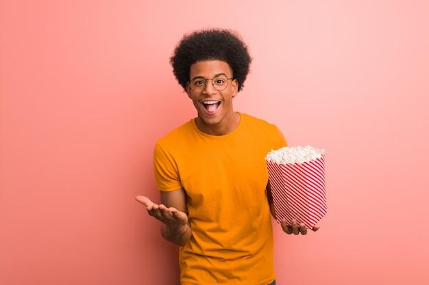 Giovane afroamericano che tiene un secchio del popcorn sorpreso e colpito