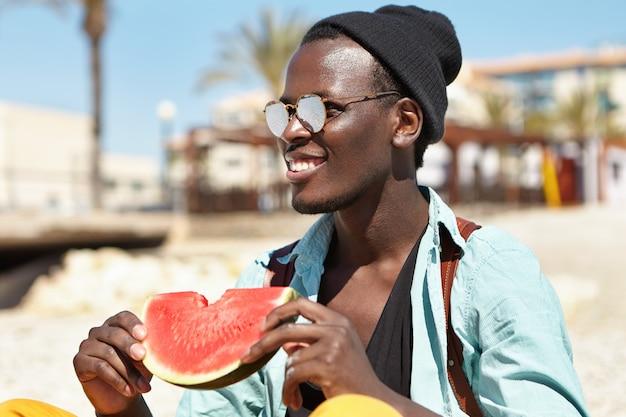 Giovane afroamericano felice alla moda allegro che ha picnic sulla spiaggia con gli amici, tenendo la fetta di anguria matura, guardando verso il mare con un ampio sorriso, guardando i delfini che giocano in acqua