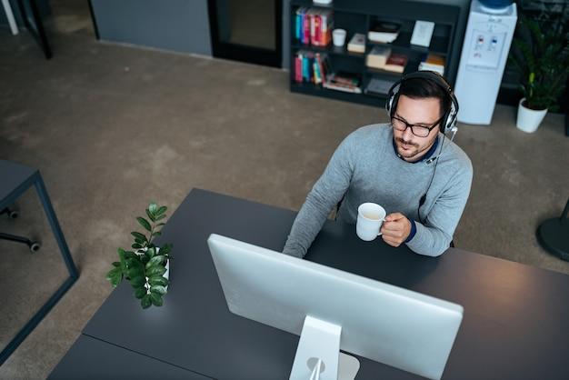 Giovane agente bel centro di supporto seduto alla sua scrivania. lavorare e bere caffè.