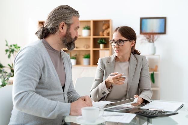 Giovane agente immobiliare con touchpad seduto accanto al suo cliente mentre gli spiega i termini dell'accordo