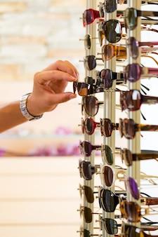 Giovane agli occhiali da sole di acquisto dell'ottico