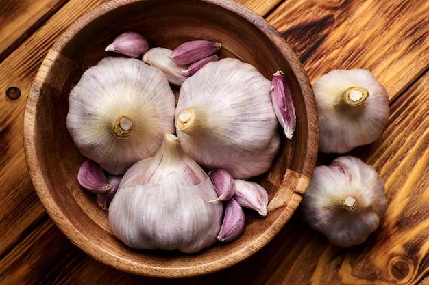 Giovane aglio fresco in una tazza di legno su una tavola di legno.
