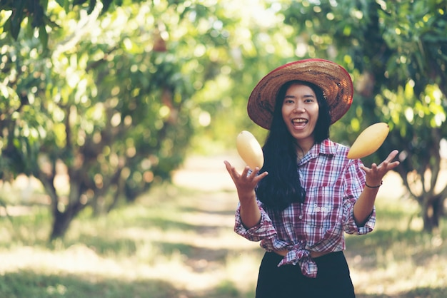 Giovane agricoltore asiatico che seleziona la frutta del mango in azienda agricola organica