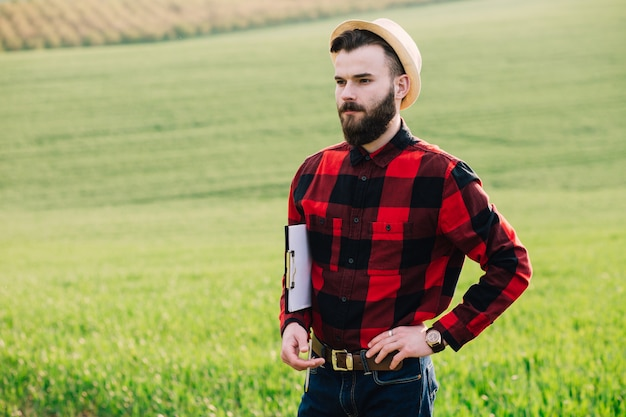 Giovane agricoltore barbuto bello con la cartella che sta nel giacimento di grano verde di inizio dell'estate