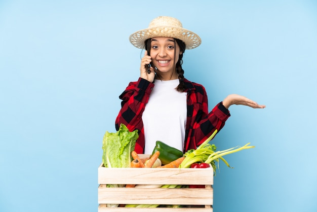 Giovane agricoltore donna con verdure fresche in un cestino di legno mantenendo una conversazione con il telefono cellulare con qualcuno