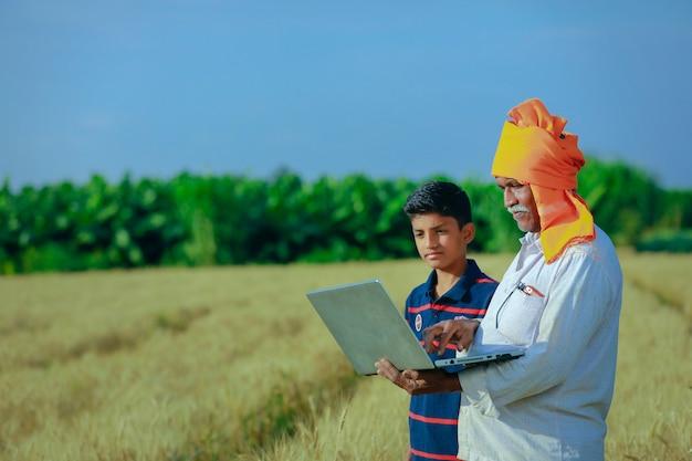 Giovane agricoltore indiano nel suo campo di grano con il suo bambino