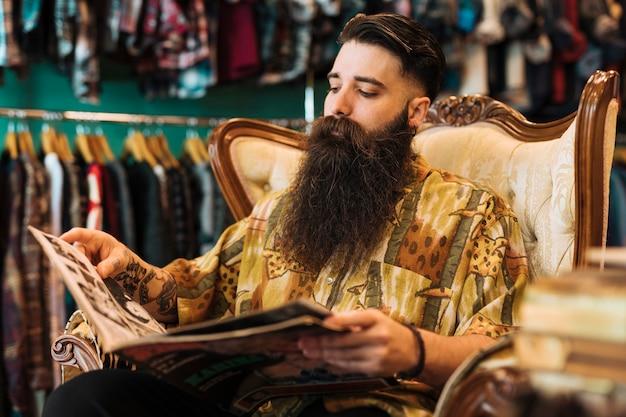 Giovane alla moda barbuto che si siede sulla sedia che esamina rivista nel negozio