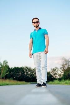 Giovane alla moda che porta polo blu e jeans bianchi su un vuoto