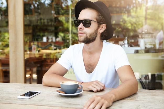Giovane alla moda in occhiali da sole alla moda e camicia bianca con scollo av che riposa nella caffetteria sul marciapiede, bevendo cappuccino
