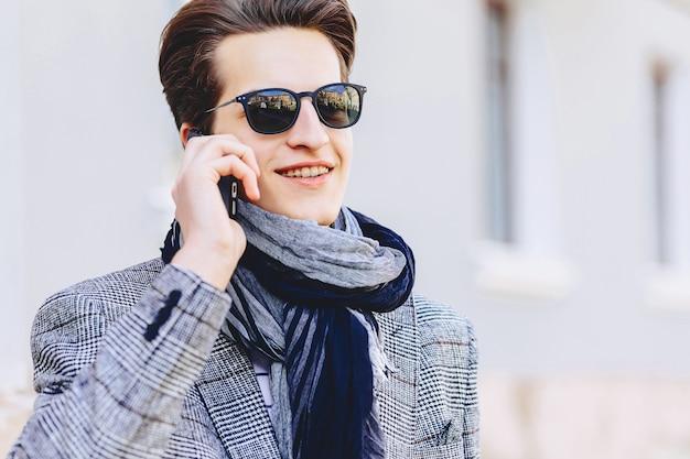 Giovane alla moda in occhiali da sole con il telefono sulla strada