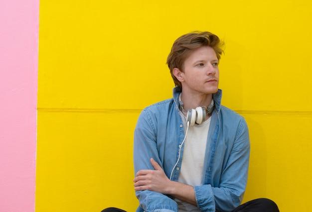 Giovane allegro che ascolta la musica con le cuffie su fondo giallo con lo spazio della copia.