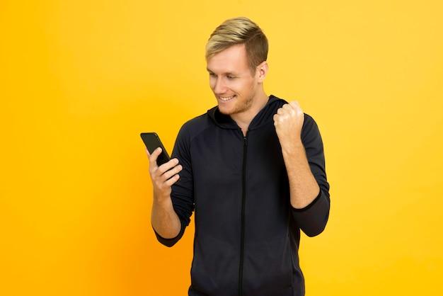 Giovane allegro del ritratto che gioca telefono cellulare isolato sopra fondo giallo