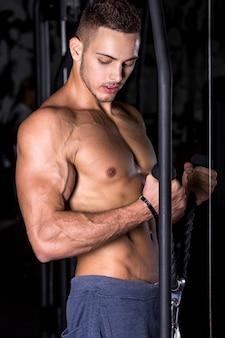 Giovane allenamento bodybuilder sul crossover
