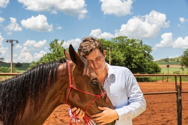 Giovane allevatore di cavalli che conforta un cavallo nel ranch