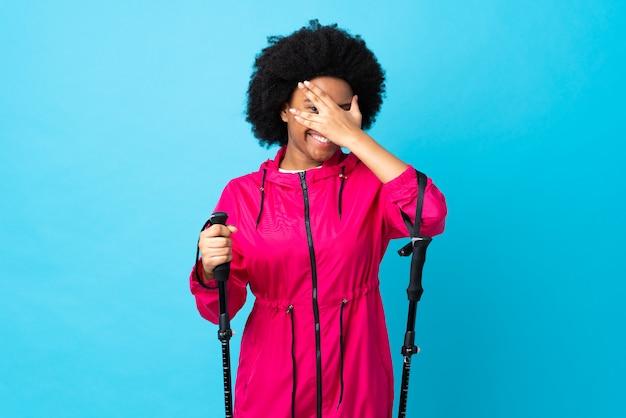 Giovane americano africano con zaino e bastoncini da trekking sul muro blu che copre gli occhi a mano e sorridendo