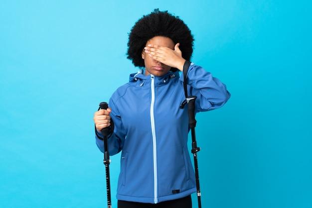 Giovane americano dell'africa con lo zaino e pali di trekking isolati sul rivestimento blu della parete osserva a mano. non voglio vedere qualcosa
