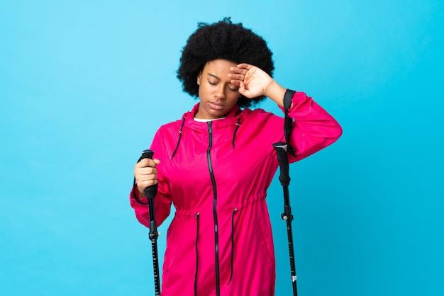 Giovane americano dell'africa con lo zaino e pali di trekking isolati sulla parete blu con l'espressione stanca e malata