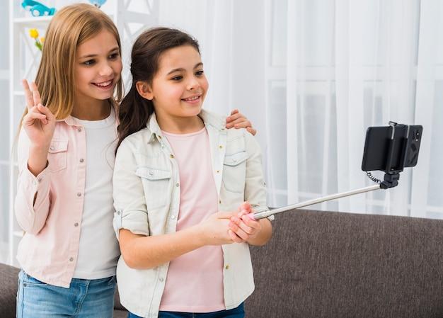 Giovane amica prendendo foto selfie con un bastone selfie
