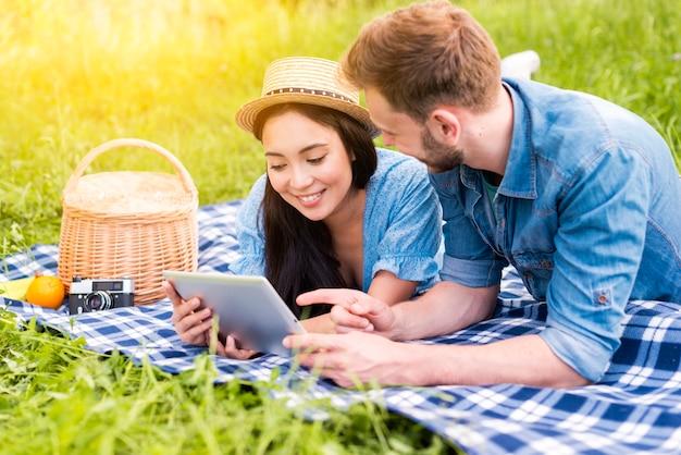 Giovane amorevole coppia navigare sul web utilizzando la tavoletta in campagna